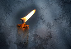 Little candle flame behind frozen window glass. Closeup photo of little candle flame behind frozen window glass Royalty Free Stock Image