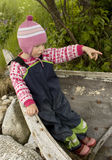 Little capt'n. Little girl (3 years old) playing in an old wooden boat, pointing the direction Royalty Free Stock Photo