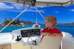 Little captain. Little boy sitting on captain seat in the boat Stock Photos