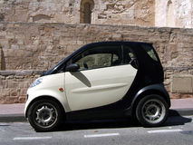 Little car. Little white and black car in the street with a stones background royalty free stock photo