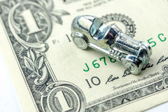 Little car made of chrome is laying on one dollar banknote Royalty Free Stock Photo