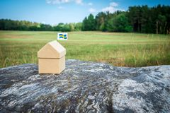 Little cardboard house in Swedish summer landscape. Little cardboard house with a Swedish flag in Scandinavian summer landscape stock photo