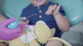 Little carefree boy sitting in the chair in dental office. Cute child playing with plush toy. Dental treatment, medical. Concept stock video footage