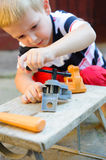 Little carpenter. Concentrated little boy is playing in carpenter Stock Photography