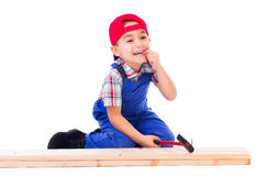 Little carpenter hit his finger while nailing. Little carpenter hit his own finger while nailing Royalty Free Stock Photography