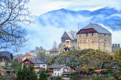 Little castle in Southern Tirol, Italy. Misty evening view of an alpine village in Southern Tirol by Bolzano, Italy Stock Photography