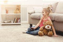 Beautiful casual little girl watching tv while sitting on the floor at home. Little casual girl watching tv at home. Female kid sitting on the floor carpet with Royalty Free Stock Photos