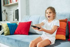 Little casual girl watching tv at home. Female kid sitting on sofa with TV remote and switching channels. Little casual girl watching tv at home. Female kid Stock Photos