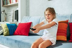 Little casual girl watching tv at home. Female kid sitting on sofa with TV remote and switching channels. Little casual girl watching tv at home. Female kid Stock Image
