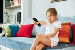 Little casual girl watching tv at home. Female kid sitting on sofa with TV remote and switching channels. Little casual girl watching tv at home. Female kid Stock Photo