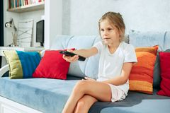 Little casual girl watching tv at home. Female kid sitting on sofa with TV remote and switching channels. Little casual girl watching tv at home. Female kid Royalty Free Stock Photo