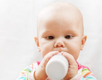 Little Caucasian baby with bottle of milk Stock Images