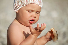 Little Caucasian baby eats croissant Stock Photos