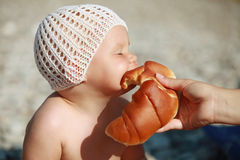Little Caucasian baby eats croissant with pleasure Stock Image