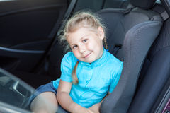Little Caucasian blond girl in car safety seat Royalty Free Stock Photos