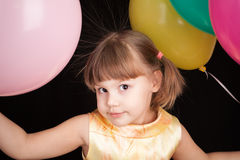 Little Caucasian blond girl with colorful balloons Royalty Free Stock Photo
