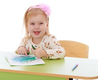 Little Caucasian blond girl draws with pencils Royalty Free Stock Image
