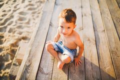 Little Caucasian boy child sitting on wooden pier sandy beach, summer time, sea vacation near water. The theme is the flow of time royalty free stock image