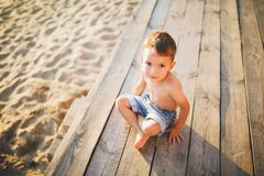 Little Caucasian boy child sitting on wooden pier sandy beach, summer time, sea vacation near water. The theme is the flow of time royalty free stock photography