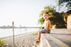 Little Caucasian boy child sitting on wooden pier sandy beach, summer time, sea vacation near water. The theme is the flow of time stock image