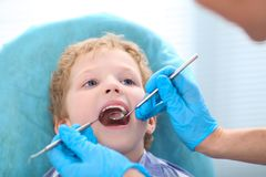 Young curly Caucasian boy at the dentist`s clinic. royalty free stock image