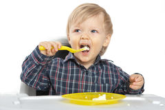 Little caucasian boy eat breakfast at baby table Royalty Free Stock Photo