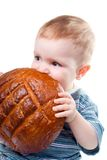 A little Caucasian boy eating a bread. Royalty Free Stock Images