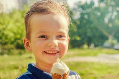 Little caucasian boy enjoying a melting ice cream on a sweltering hot summer day. Green summer trees in background. 3 year old caucasian boy enjoying a melting royalty free stock photo