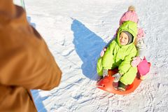 Little kids on sled ride. Little Caucasian boy and his sister sitting on sled and squinting from bright sun on beautiful winter afternoon, father pulling them Stock Photos