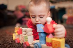 Boy playing with a wooden toy train. Little Caucasian boy playing with a colourful wooden toy train on the carpet in the living room in the house royalty free stock photo
