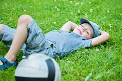Little caucasian boy resting on grass Stock Images