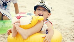 Little Caucasian boy in sailor suit and cap sitting on the beach in swim ring and laughs. Baby sitting om the beach with swim ring Royalty Free Stock Images