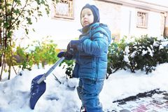 Little caucasian boy shovels snow in the yard with beautiful snowy rose bushes. Child with shovel plays outdoors in winter. Childr. En hepling, family duties stock photography