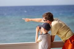 Family at vacation. Little caucasian boy using binoculars and his young father pointing with finger and showing something, exploration and vacation concept Stock Images