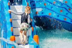 Free Little Caucasian Boy With Blond Hair Climbing The Water Slide In The Children Pool. Trickles Of Water Everywhere, Wet T-shirt And Royalty Free Stock Images - 193219029