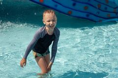 Free Little Caucasian Boy With Blond Hair Laughing In The Middle Of Children Pool. Trickles Of Water Everywhere, Wet T-shirt And Pants, Royalty Free Stock Photos - 193228928