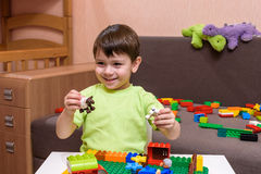 Little caucasian child playing with lots of colorful plastic blocks indoor. Kid boy wearing shirt and having fun building creating royalty free stock photo