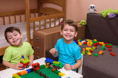 Little caucasian child playing with lots of colorful plastic blocks indoor. Kid boy wearing shirt and having fun building creating. Two little caucasian friends Royalty Free Stock Photo