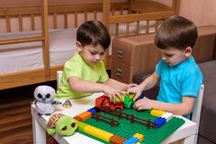 Little caucasian child playing with lots of colorful plastic blocks indoor. Kid boy wearing shirt and having fun building creating. Two little caucasian friends Stock Photo