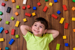 Little caucasian child playing with lots of colorful plastic blocks indoor. Kid boy wearing shirt and having fun building creating. Little caucasian child Royalty Free Stock Photography