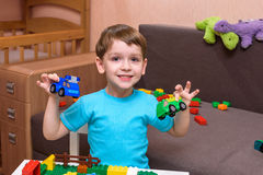 Little caucasian child playing with lots of colorful plastic blocks indoor. Kid boy wearing shirt and having fun building creating. Little caucasian child Royalty Free Stock Photo