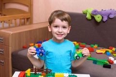 Little caucasian child playing with lots of colorful plastic blocks indoor. Kid boy wearing shirt and having fun building creating. Little caucasian child Royalty Free Stock Photos