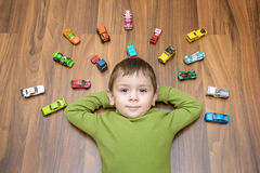 Little caucasian child playing with lots of toy cars indoor. Kid boy wearing green shirt. Happy preschool having fun at home or nu. Rsery Royalty Free Stock Photo