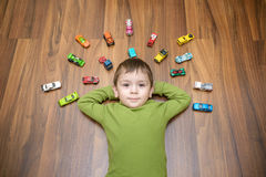 Little caucasian child playing with lots of toy cars indoor. Kid boy wearing green shirt. Happy preschool having fun at home or nu. Rsery stock photo