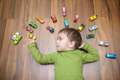 Little caucasian child playing with lots of toy cars indoor. Kid boy wearing green shirt. Happy preschool having fun at home or nu. Rsery Royalty Free Stock Photography
