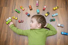 Little caucasian child playing with lots of toy cars indoor. Kid boy wearing green shirt. Happy preschool having fun at home or nu. Rsery Stock Images