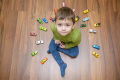 Little caucasian child playing with lots of toy cars indoor. Kid boy wearing green shirt. Happy preschool having fun at home or nu. Rsery Royalty Free Stock Images