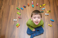 Little caucasian child playing with lots of toy cars indoor. Kid boy wearing green shirt. Happy preschool having fun at home or nu. Rsery Royalty Free Stock Image