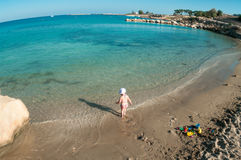 Kid playing on sandy beach of Mediterranean sea Stock Photo