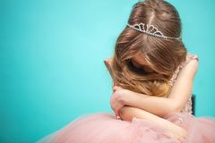 Little Caucasian female child in pink dress with naughty and resentful face expression. stock photos